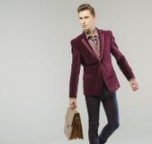 Gut aussehender Mann, der die Lederhandtasche trägt Lizenzfreies Stockfoto
