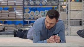 Gut aussehender Mann, der die orthopädische Matratze, im Geschäft liegend auf einem neuen Bett wählt stock footage