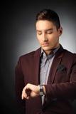 Gut aussehender Mann, der die Zeit auf seiner Armbanduhr überprüft Stockbild