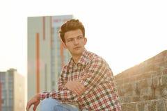 Gut aussehender Mann, der draußen auf Steintreppe sitzt Lizenzfreies Stockbild