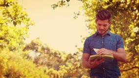 Gut aussehender Mann, der ein Buch im Park liest stock video footage
