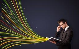 Gut aussehender Mann, der ein Buch liest, während bunte Linien herauskommen Stockbild