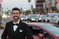 Gut aussehender Mann, der ein elegantes Smoking in der Stadt tragend lächelt Stockfotos