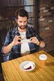 Gut aussehender Mann, der ein Foto seines Kuchens und Kaffees macht Stockfoto