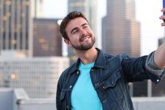 Gut aussehender Mann, der ein selfie mit einem Stadtbild nimmt Stockfoto