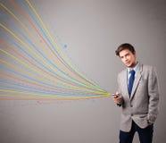 Gut aussehender Mann, der ein Telefon mit bunten abstrakten Linien hält Lizenzfreie Stockbilder