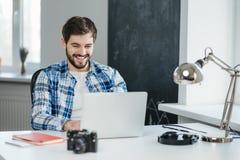 Gut aussehender Mann, der ein Videogespräch auf Laptop hat lizenzfreies stockbild