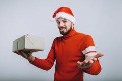 Gut aussehender Mann, der ein Weihnachtsgeschenk hält Getrennt auf weißem Hintergrund stockfotografie