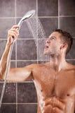 Gut aussehender Mann, der eine Dusche nimmt Stockbild