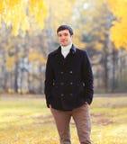 Gut aussehender Mann, der eine schwarze Manteljacke am Herbsttag trägt Stockbild