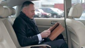 Gut aussehender Mann, der eine Tablette im Auto verwendet stock video