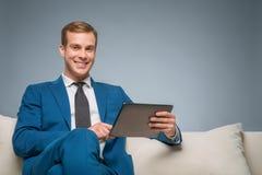 Gut aussehender Mann, der eine Tablette verwendet Lizenzfreie Stockbilder