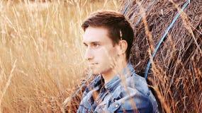 Gut aussehender Mann, der in einem Getreidefeld sitzt Lizenzfreie Stockbilder