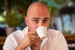 Gut aussehender Mann, der einen geschmackvollen Tasse Kaffee genießt Lizenzfreies Stockbild