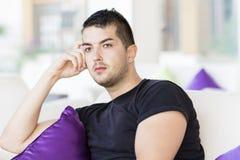 Gut aussehender Mann, der in einer Hotellobby auf weißem Sofa mit purpurroten Kissen sich entspannt Stockfotografie
