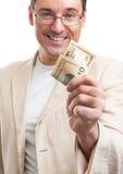 Gut aussehender Mann, der einige Dollar gibt Stockbild