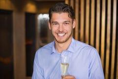Gut aussehender Mann, der Flöte des Champagners hält Stockfotos