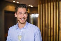 Gut aussehender Mann, der Flöte des Champagners hält Stockfoto
