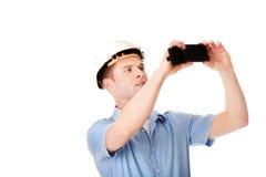 Gut aussehender Mann, der Fotos durch seinen Handy macht Lizenzfreies Stockfoto