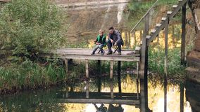 Gut aussehender Mann in der Freizeitbekleidung fängt Fische mit seinem Kind, das auf hölzernem Dock mit Stangen sitzt und betrach stock video