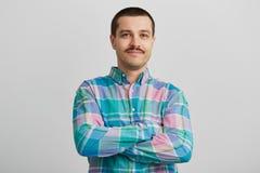 Gut aussehender Mann, der gerade in camera schaut, halten Querhände Lokalisiert auf weißer Wand Stockfotografie