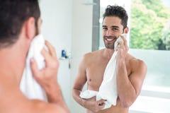 Gut aussehender Mann, der Gesicht beim Schauen im Spiegel abwischt Stockbild