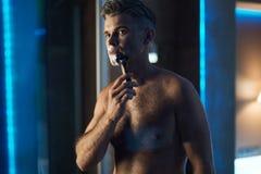 Gut aussehender Mann, der Gesicht im Badezimmer rasiert Gesichtshaar-Pflegen lizenzfreie stockfotos
