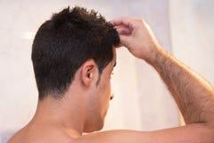 Gut aussehender Mann, der Haargel anwendet stockfoto