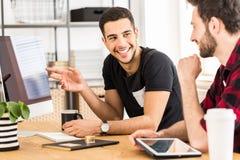 Gut aussehender Mann, der herein seinem Kollegen etwas auf einem Computer zeigt lizenzfreies stockfoto