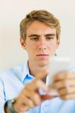 Gut aussehender Mann, der intelligenten Handy verwendet Stockfotografie