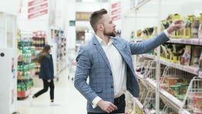 Gut aussehender Mann in der Jacke wählt Gewürze in einem Supermarkt stock video