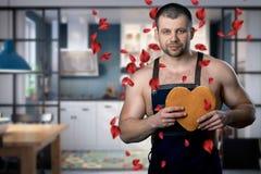 Gut aussehender Mann, der in der Küche mit einem Keksherzen in seinen Händen steht rosafarbene Blumenblätter, die auf den Mann fa stockbild
