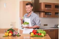 Gut aussehender Mann, der Kalk für frischen Salat zusammendrückt Stockbilder