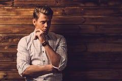 Gut aussehender Mann, der kariertes Hemd im hölzernen ländlichen Hausinnenraum trägt stockbild