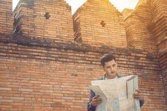 Gut aussehender Mann, der Kartenpapier mit dem Finden des Standorts für Reise hält Stockbild