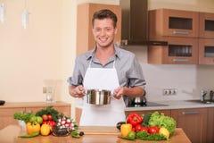 Gut aussehender Mann, der Kasserolle für neue vegatebles hält Lizenzfreie Stockbilder