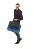 Gut aussehender Mann in der Klage mit Einkaufstaschen Stockfotografie