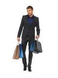 Gut aussehender Mann in der Klage mit Einkaufstaschen Stockfotos