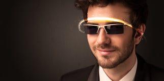 Gut aussehender Mann, der mit futuristischen High-Techen Gläsern schaut Stockfotos
