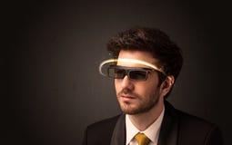 Gut aussehender Mann, der mit futuristischen High-Techen Gläsern schaut Lizenzfreie Stockfotos
