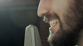 Gut aussehender Mann, der mit Mikrofon singt stockfotografie