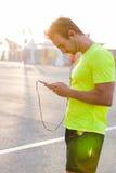 Gut aussehender Mann, der Musik auf Kopfhörern am intelligenten Telefon beim Stillstehen hört Stockbilder