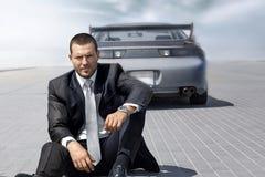 Gut aussehender Mann, der nahe seinem blauen Auto sitzt Lizenzfreie Stockfotos