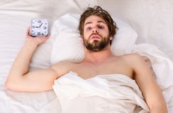 Gut aussehender Mann, der oben seine Arme gähnt und ausdehnt Netter junger Mann wacht auf, nachdem er morgens geschlafen hat E stockfotografie