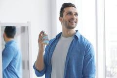 Gut aussehender Mann, der Parfüm verwendet stockbild