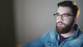Gut aussehender Mann, der PC verwendet und dann lächelt stock footage
