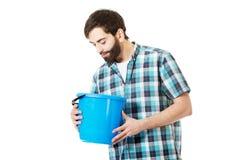 Gut aussehender Mann, der Plastikeimer untersucht Stockbild