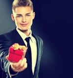 Gut aussehender Mann, der rote Geschenkbox gibt Stockfoto