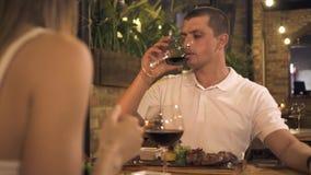 Gut aussehender Mann, der Rotwein vom Glas während romantisches Abendessen trinkt, wenn Restaurant geglättet wird Trinkender Wein stock video