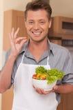Gut aussehender Mann, der Schüssel frischen Salat hält Stockbild
